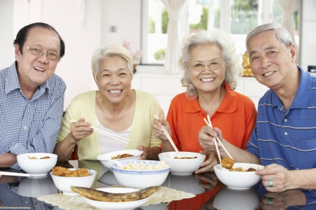 Group Of Senior Chinese Friends Eating Meal At Home photo