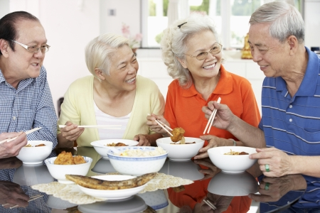 asian elderly: Group Of Senior Chinese Friends Eating Meal At Home Stock Photo