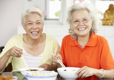 senior asian: Two Senior Chinese Women Sitting At Home Eating Meal