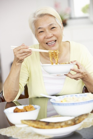Senior Chinese Woman Sitting At Home Eating Meal photo