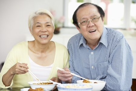 Senior Chinese Couple Sitting At Home Eating Meal photo