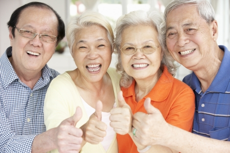 senior female: Group Of Senior Chinese Friends Relaxing On Sofa At Home Stock Photo
