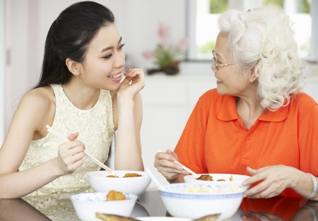 grown ups: Chinese Mother And Adult Daughter Eating Meal Together