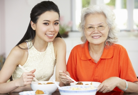 Chinese Mother And Adult Daughter Eating Meal Together Stock Photo - 18709871