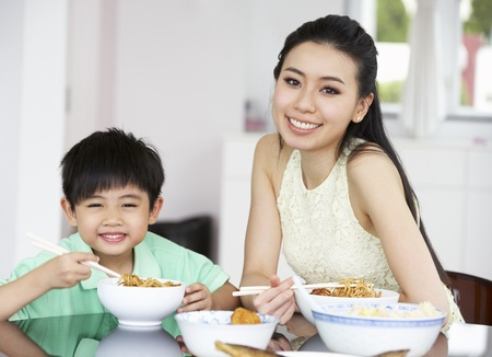 Chinese Mother And Son Sitting At Home Eating A Meal photo