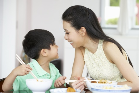 rice noodles: Chinese Mother And Son Sitting At Home Eating A Meal