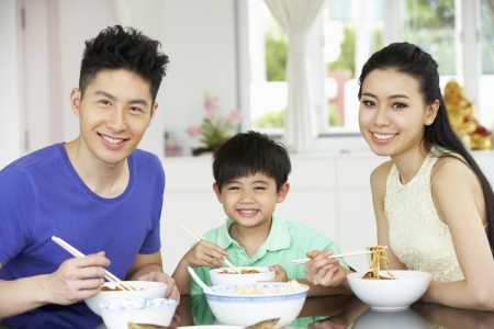 familia comiendo: Familia chino sentado en casa comiendo una comida