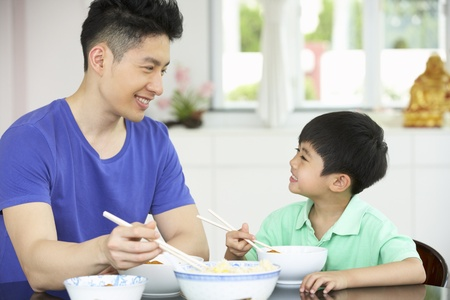 Chinese Father And Son Sitting At Home Eating A Meal photo