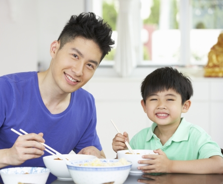 Chinese Father And Son Sitting At Home Eating A Meal Stock Photo - 18709156