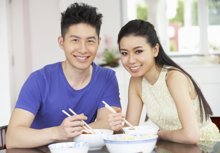 Young Chinese Couple Sitting At Home Eating Meal photo