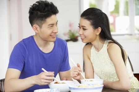 pareja comiendo: Pareja joven sentado en chino comida casera Comer