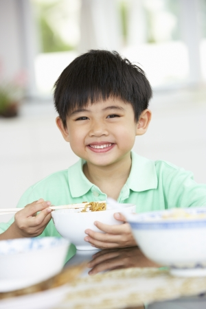 Young Chinese Boy Sitting At Home Eating Meal photo