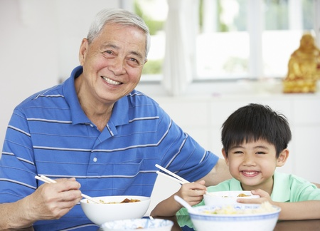 Portrait Of Chinese Grandfather And Grandson Eating Meal Together photo