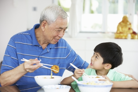 senior eating: Portrait Of Chinese Grandfather And Grandson Eating Meal Together