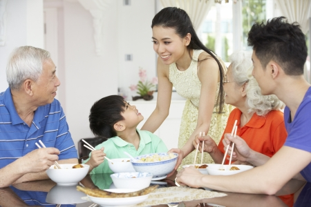 family of five: Portrait Of Multi-Generation Chinese Family Eating Meal Together Stock Photo