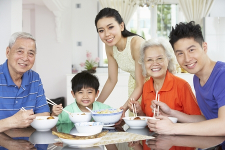 noodle bowl: Portrait Of Multi-Generation Chinese Family Eating Meal Together Stock Photo