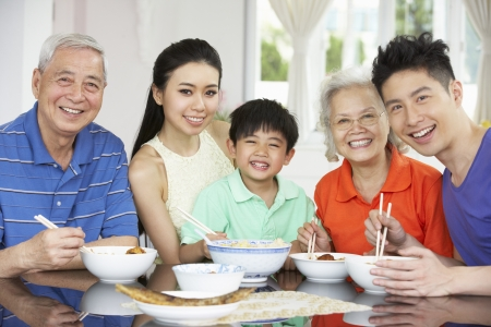 chinese family: Portrait Of Multi-Generation Chinese Family Eating Meal Together Stock Photo