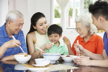 three generation: Portrait Of Multi-Generation Chinese Family Eating Meal Together Stock Photo