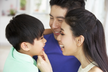 Head And Shoulders Portrait Of Chinese Family Together At Home photo