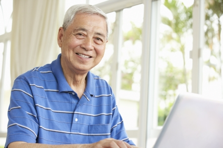 man couch: Senior Chinese Man Sitting At Desk Using Laptop At Home Stock Photo