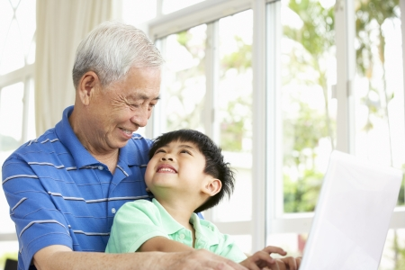 grandfather and grandson: Chinese Grandfather And Grandson Sitting At Desk Using Laptop At Home Stock Photo