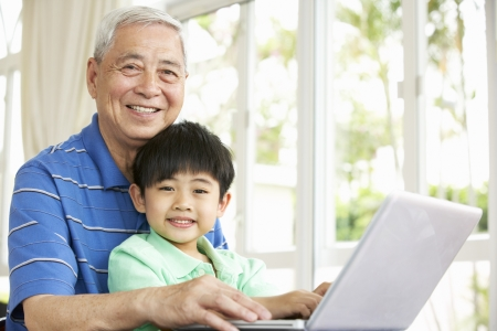 Chinese Grandfather And Grandson Sitting At Desk Using Laptop At Home photo