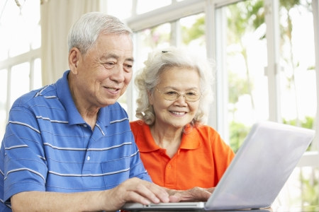 Senior Chinese Couple Sitting At Desk Using Laptop At Home photo