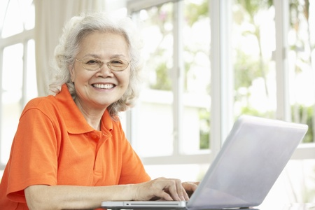 Senior Chinese Woman Sitting At Desk Using Laptop At Home photo