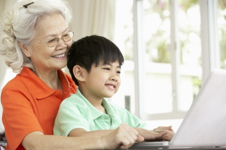 Chinese Grandmother And Grandson Sitting At Desk Using Laptop At Home photo