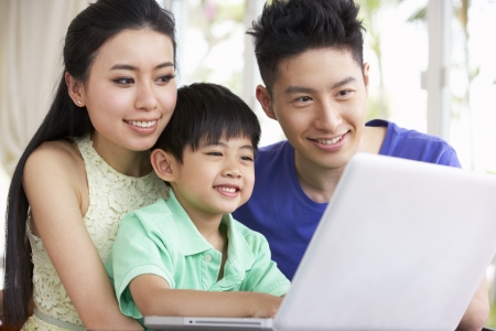 Chinese Family Sitting At Desk Using Laptop At Home photo