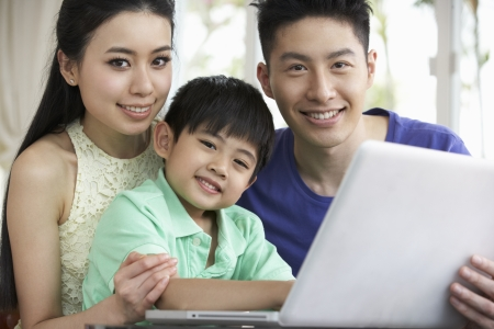 chinese family: Chinese Family Sitting At Desk Using Laptop At Home