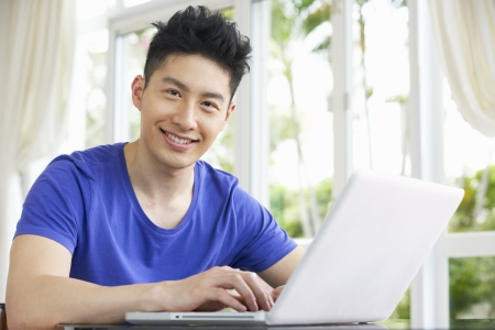 asian laptop: Young Chinese Man Sitting At Desk Using Laptop At Home Stock Photo