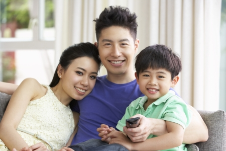 Chinese Family Sitting And Watching TV On Sofa Together photo