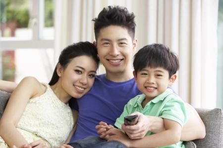 Famille Chinois assis à regarder la télévision sur canapé ensemble