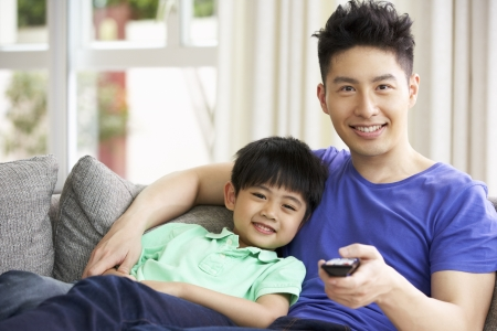 Chinese Father And Son Sitting And Watching TV On Sofa Together Stock fotó
