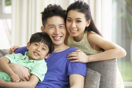 Chinese Family Sitting And Relaxing On Sofa Together At Home Foto de archivo