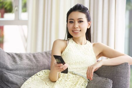 Young Chinese Woman Sitting And Watching TV On Sofa At Home photo