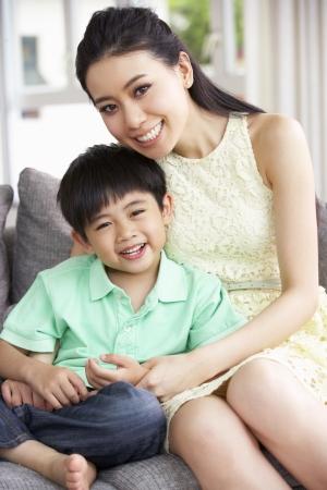 mama e hijo: Madre china e hijo se sienta en el sof� en casa Juntos