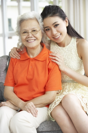 grown ups: Portrait Of Chinese Mother With Adult Daughter Relaxing At Home