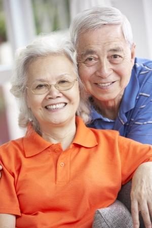 senior couple: Senior Chinese Couple Relaxing On Sofa At Home Stock Photo