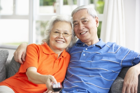 Senior Chinese Couple Watching TV On Sofa At Home photo