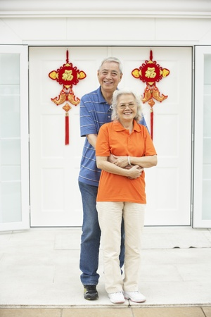 Senior Chinese Couple Outside Home Decorated With Welcoming Feng Shui Banners photo