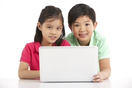 bambini cinesi: Fotografia da studio di due bambini cinesi con il computer portatile