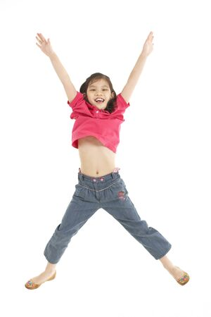 7 year old girl: Studio Shot Of Chinese Girl Jumping In Air Stock Photo