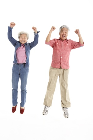 Studio Shot Of Chinese Senior Couple Jumping In Air photo