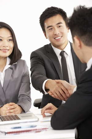 Studio Shot Of Two Chinese Businessmen Shaking Hands During Meeting Stock Photo - 18709528