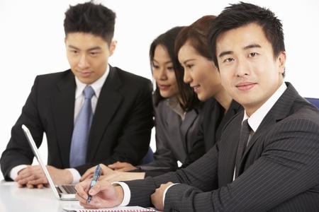 Studio Shot Of Chinese Businesspeople Having Meeting Stock Photo - 18709459