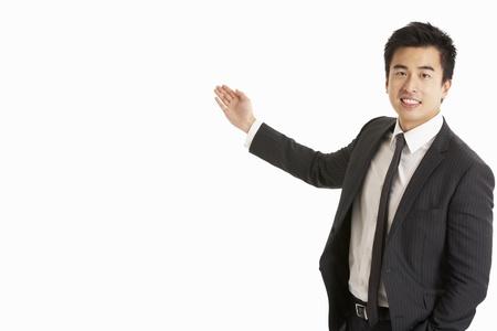 businessman standing: Studio Portrait Of Chinese Businessman Gesturing