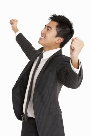 excited man: Studio Portrait Of Chinese Businessman Celebrating