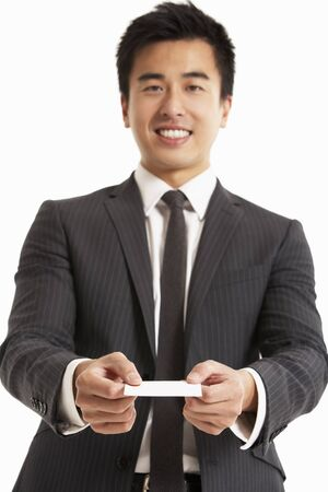 welcome smile: Studio Portrait Of Chinese Businessman Offering Business Card